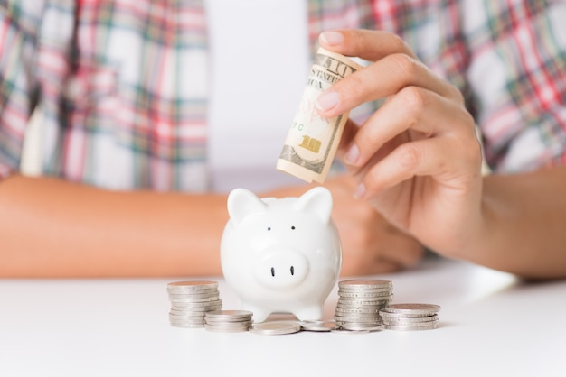 Mão da mulher que põe a moeda do dinheiro no mealheiro e na pilha de moedas.
