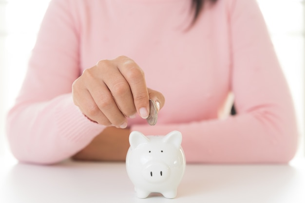 Mão da mulher que põe a moeda no mealheiro. economizando dinheiro