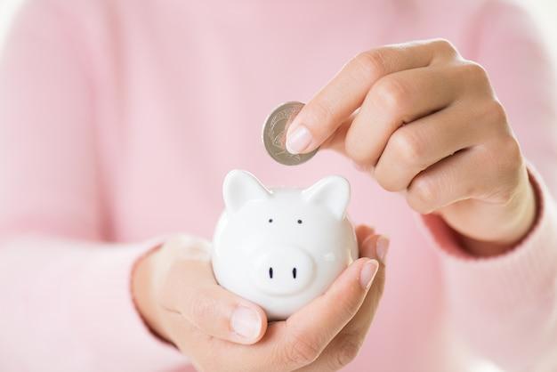 Mão da mulher que põe a moeda no mealheiro. economizando riqueza de dinheiro e conceito financeiro