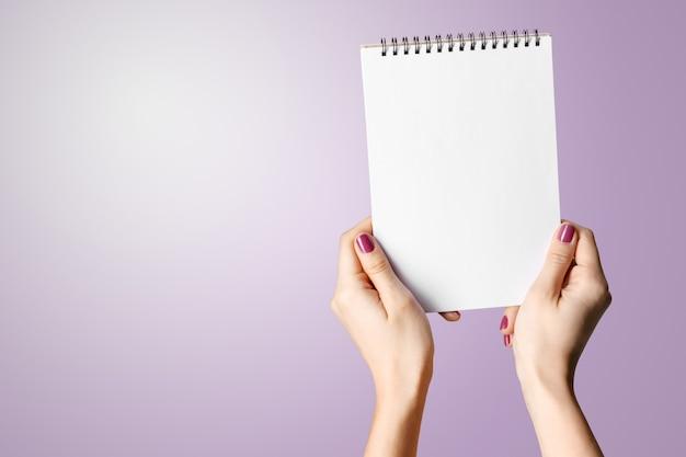 Mão da mulher que prende o bloco de notas espiral em branco.
