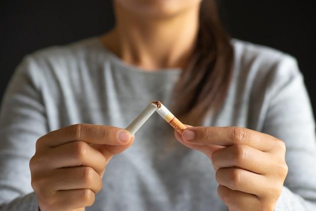 Mão da mulher que quebra, esmagando ou destruindo cigarros no fundo preto.