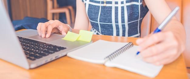 Mão da mulher que trabalha em um computador e que escreve em um bloco de notas com uma pena no escritório bandeira de web.