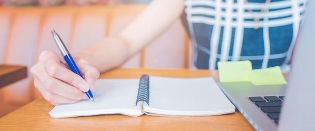 Mão da mulher que trabalha em um computador e que escreve em um bloco de notas com uma pena no escritório.