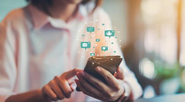 Mão da mulher que usa o smartphone e mostre meios sociais do ícone da tecnologia. rede social de conceito.