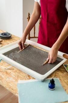 Mão da mulher, removendo o secador de madeira da polpa de papel