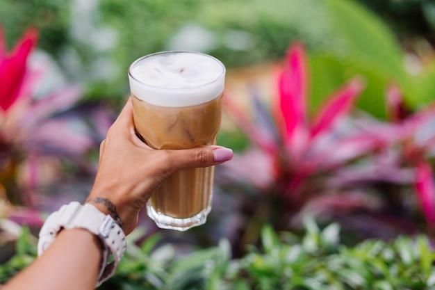 Mão da mulher segurando café com leite gelado sobre arbustos tropicais verdes