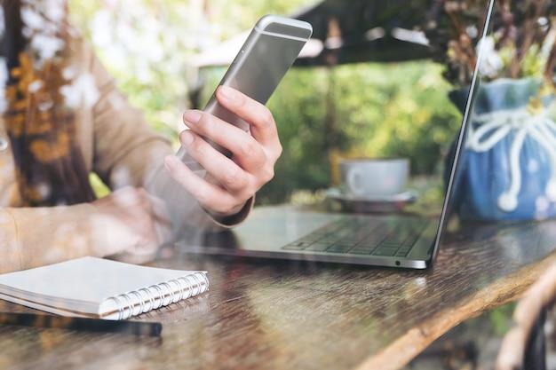 Mão da mulher segurando e olhando para o telefone inteligente enquanto estiver usando o laptop no café
