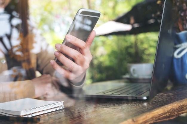 Mão da mulher segurando e olhando para o telefone inteligente enquanto estiver usando o laptop no café Foto Premium