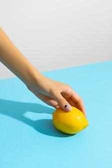 Mão da mulher segurando limão sobre fundo azul. layout criativo da moda da beleza com o mínimo de elegância