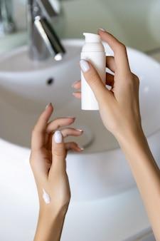 Mão da mulher segurando loção ou creme no banheiro