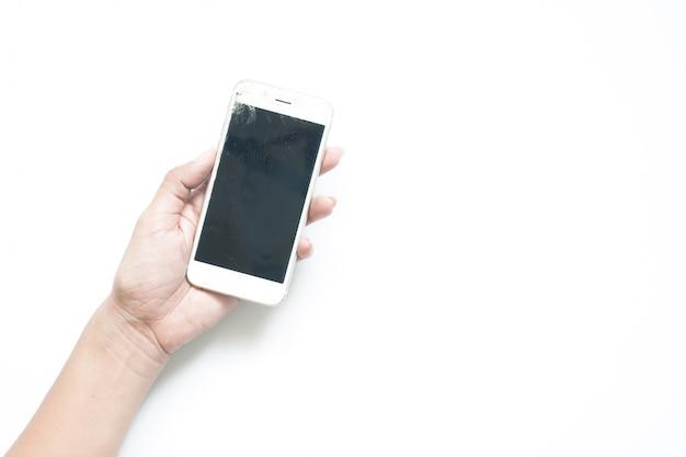 Mão da mulher segurando o dispositivo móvel de tela quebrada no fundo branco