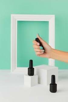 Mão da mulher segurando o frasco de esmalte sobre fundo turquesa. desenho de unhas primavera verão. layout criativo de moda beleza