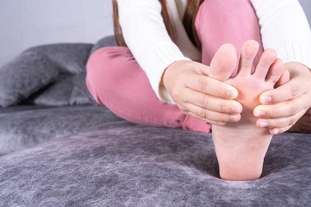 Mão da mulher segurando o pé com dor enquanto está sentado no sofá.
