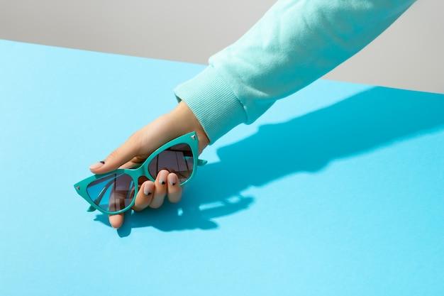 Mão da mulher segurando óculos de sol sobre fundo azul. layout criativo da moda da beleza com o mínimo de elegância