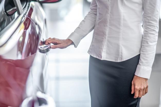 Mão da mulher tocando a porta do carro novo
