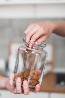 Mão da mulher tomando cookie de vidro jarra espera por uma pessoa