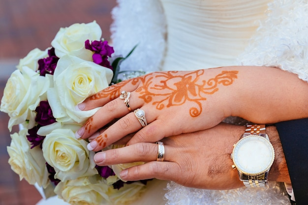 Mão da noiva com tatuagem de henna e jóias, casamento