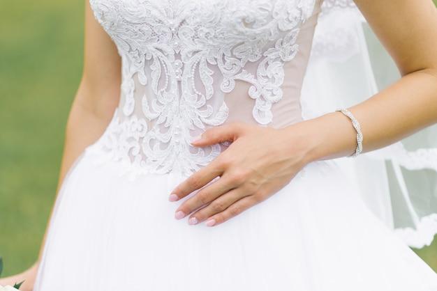 Mão da noiva, deitado sobre o vestido de casamento branco, manicure de casamento