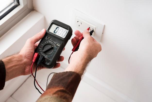 Mão da pessoa, conectando multímetro digital em casa