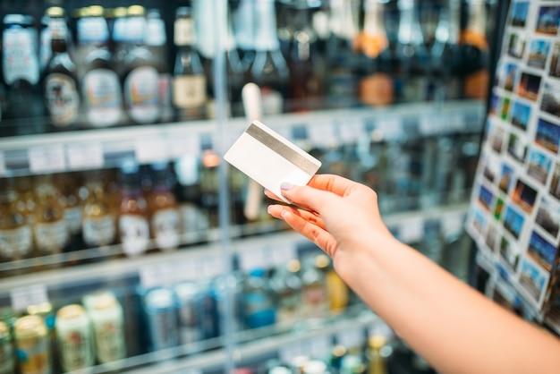 Mão da pessoa feminina com cartão de crédito, comprador no mercado de álcool. prateleiras com garrafas no fundo