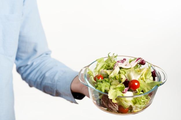 Mão da pessoa que mostra a bacia de salada saudável