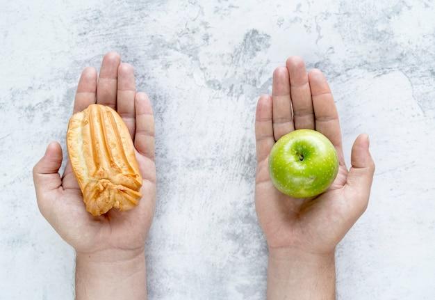 Mão da pessoa que mostra o �clair e a maçã verde sobre o fundo concreto