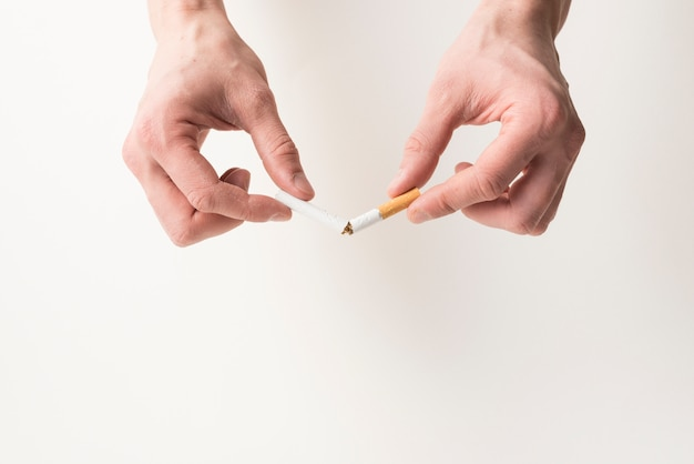 Mão da pessoa que quebra o cigarro no fundo branco