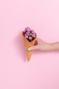 Mão da pessoa segurando buquê de flores roxas no cone waffle na frente de fundo rosa