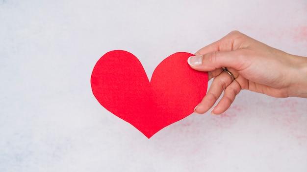 Mão da senhora com coração de papel
