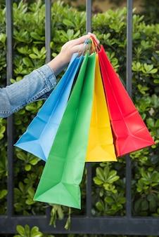 Mão da senhora com muitos sacos de compras brilhantes perto de plantas