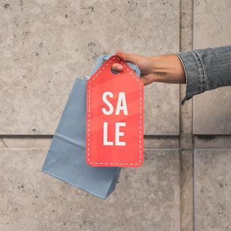 Mão da senhora com pacote de compras e tablet de venda