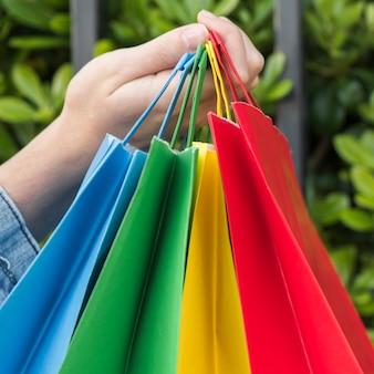 Mão da senhora com sacos de compras brilhantes