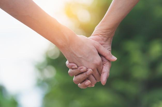 Mão da senhora e jovem senhora segurando juntos