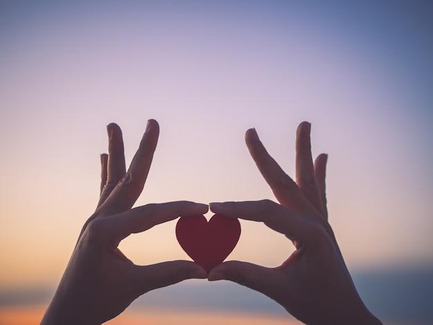 Mão da silhueta que guarda o coração bonito durante o fundo do por do sol.