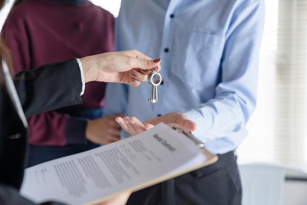 Mão dando chaves e documentos para um casal
