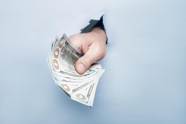 Mão dando dinheiro através de um buraco