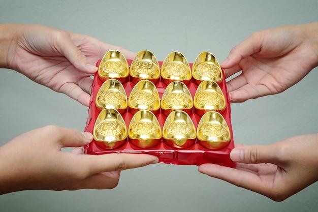 Mão dando lingote de ouro para alguém para a celebração do ano novo chinês