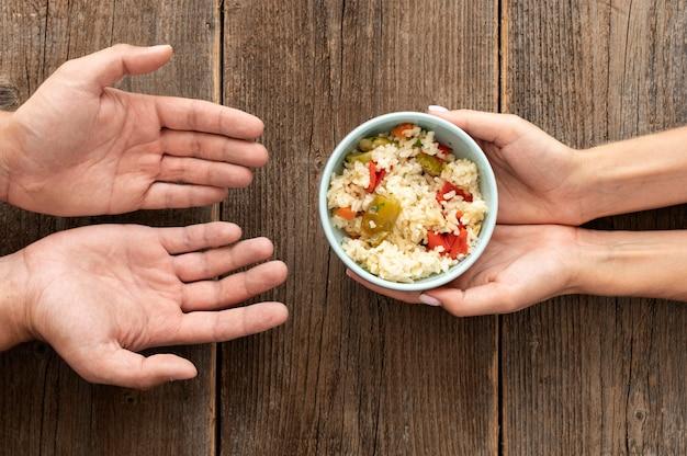 Mão dando tigela de comida para pessoa necessitada