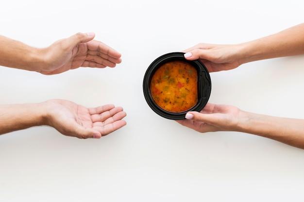 Mão dando tigela de sopa para pessoa necessitada