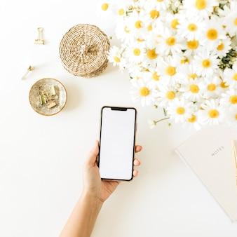 Mão das mulheres segura smartphone com tela em branco. área de trabalho da mesa do escritório em casa com buquê de flores de margarida de camomila e caderno em fundo branco
