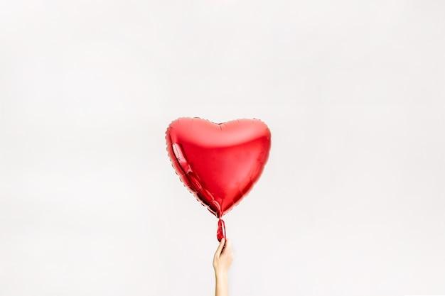 Mão das mulheres segurando um balão de forma de coração vermelho. conceito de amor