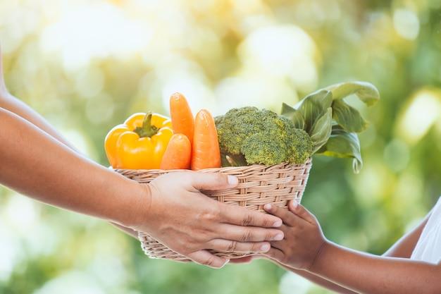 Mão de agricultor mãe dando cesta de legumes para mão de menina pequena criança no jardim