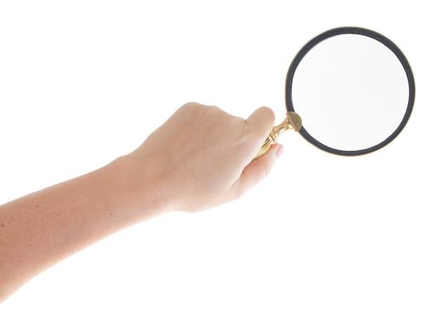 Mão de alguém segurando uma lupa isolada no fundo branco