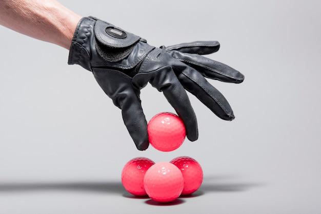 Mão de alto ângulo, colocando bolas de golfe