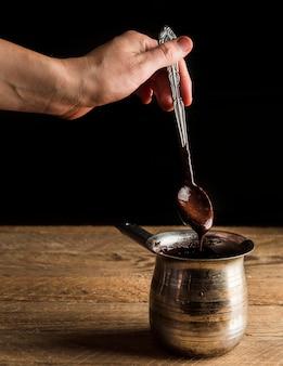 Mão de alto ângulo, segurando a colher de chá com chocolate derretido sobre panela