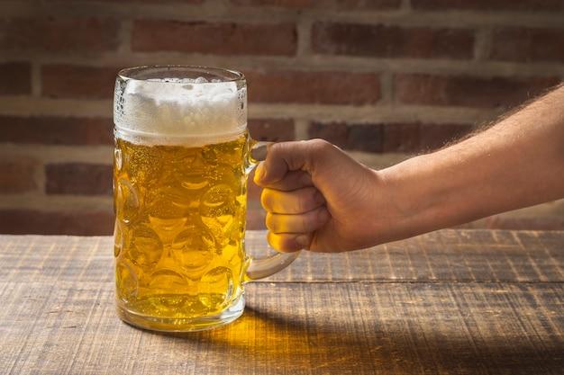 Mão de alto ângulo, segurando uma caneca de cerveja na mesa