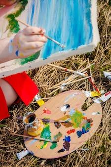 Mão de artista desenhando a imagem e paleta com tintas e pincéis no fundo da grama.