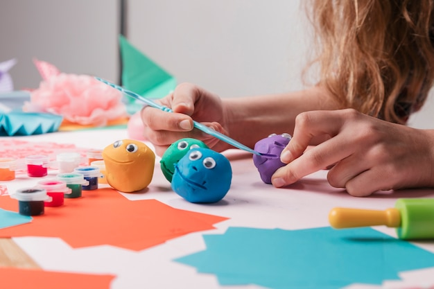 Mão de artista feminina fazendo caretas cartoon usando equipamento artesanal