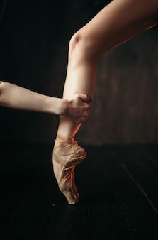 Mão de bailarina segura o pé em sapatilhas de ponta, piso de madeira preta. bailarina vestida de vermelho e preto praticando dança no palco do teatro