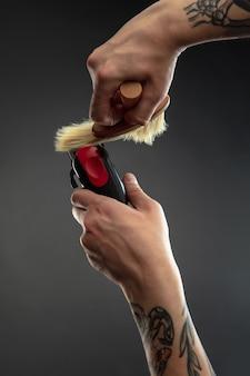 Mão de barbeiro com equipamento definido na mesa preta.